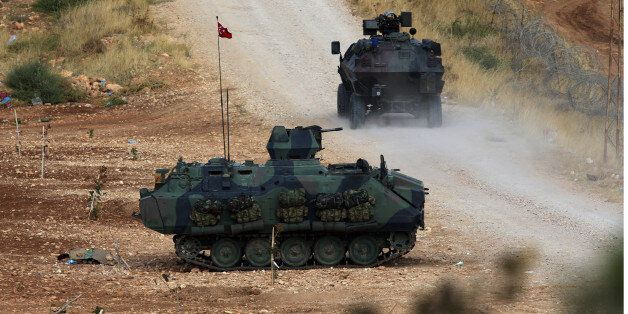 Turkish army's armored vehicles stationed near the fighting positions between Syrian Kurds and Islamic...