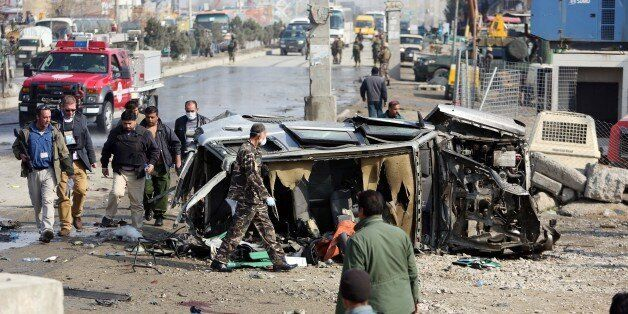 Afghan security forces inspect a British embassy vehicle which was targeted in a suicide attack in Kabul,...
