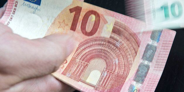 In this picture taken with a long time exposure a counterfeit money expert of the German Federal Bank...