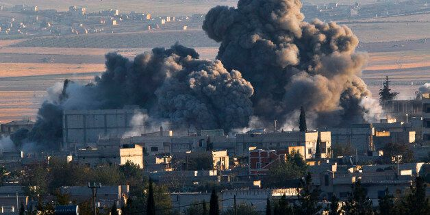 A bombs, seen top left, falls on an Islamic State position in eastern Kobani, during an airstrike by...
