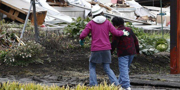 Local residents walk past a collapsed house after a strong earthquake hit the area the night before,...