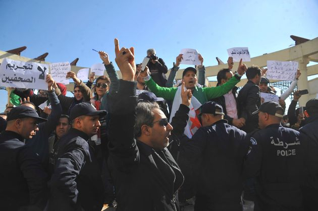 Algerian journalists are surrounded by police officers as they demonstrate at the Freedom of the Press...