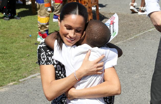 Meghan receives a hug from a young wellwisher as she visits a Justice Desk initiative in Nyanga township...