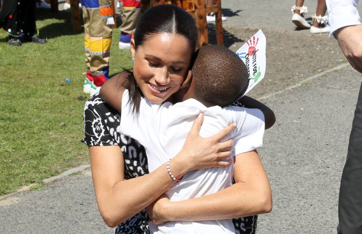 Meghan receives a hug from a young wellwisher as she visits a Justice Desk initiative in Nyanga township with Prince Harry.