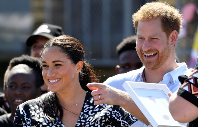 Prince Harry and his Meghan Markle smile during a stop on the first day of their African tour in Cape...