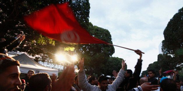 People wave a Tunisian national flag as they dance on Avenue Habib Bourguiba celebrating the second anniversary...