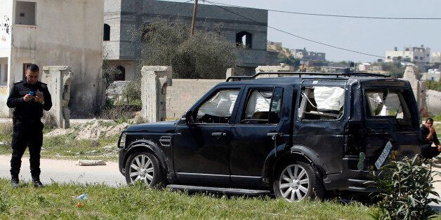 A damaged vehicle of the convoy of Palestinian Prime Minister Rami Hamdallah is seen after an explosion...
