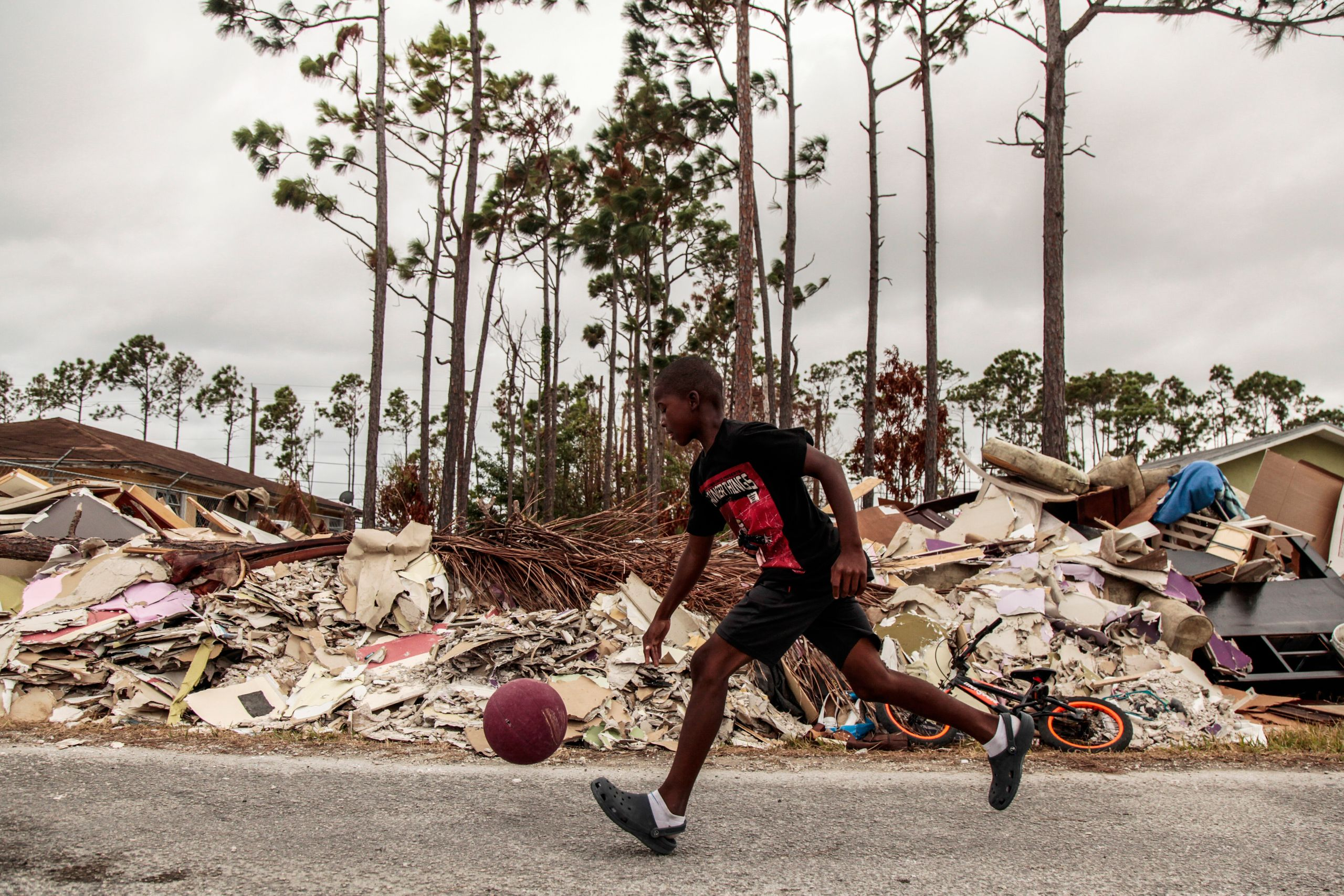 A boy dribbles a ball through debris caused by Hurricane Dorian in Freeport, Grand Bahama Sept. 21, 2019.