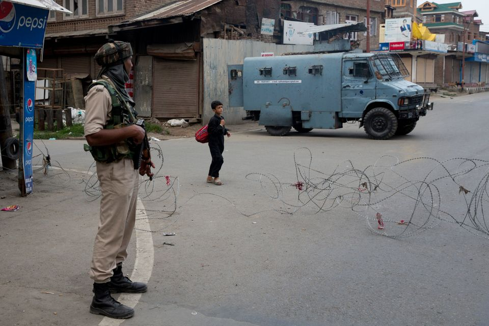 A Kashmiri boy walks past an Indian paramilitary soldier in Srinagar on August 7, 2019. Off record,...