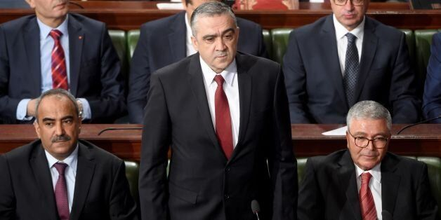 Tunisian nominated interior minister Lotfi Brahem (C) attends a parliamentary session ahead of a vote...