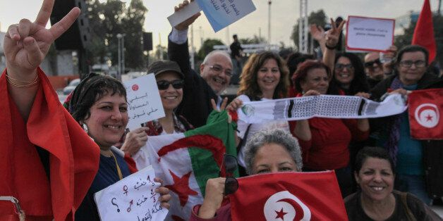 Women wave flags of Tunisia and Algeria, while raising placards and making victory signs, during a march...