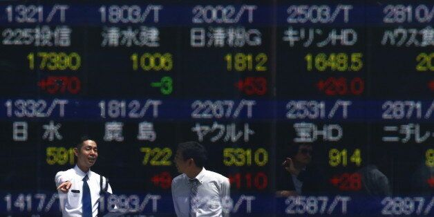 Men are refelcted in a screen displaying market indices outside a brokerage in Tokyo, Japan April 19,...