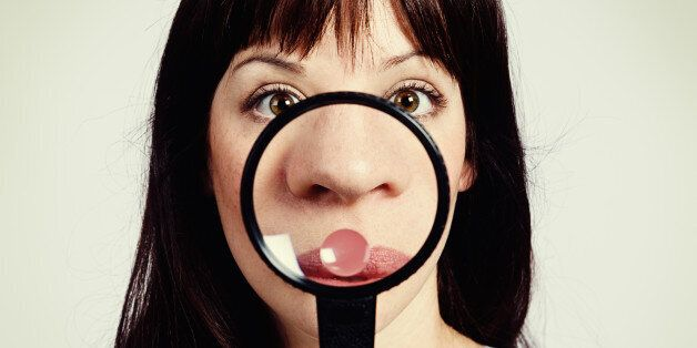 A young brunette beauty looks shocked as she examines her nose through a magnifying glass, discovering...