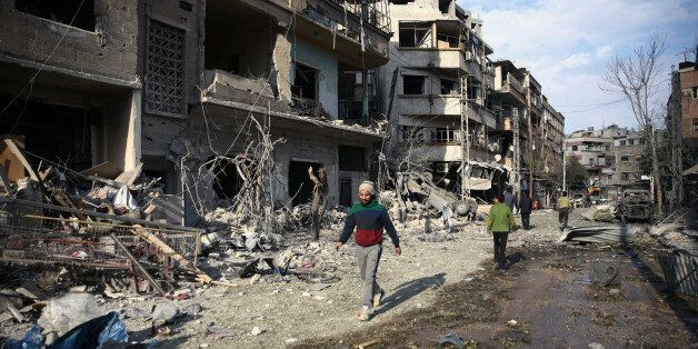 People walk through the damage, after an air raid in the besieged town of Douma, Eastern Ghouta, Damascus,...