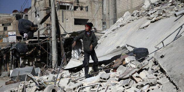 Un garçon au milieu des ruines dans la ville assiégée de Douma dans la Ghouta orientale, près de Damas,...