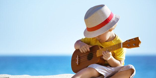 Little boy plays on Hawaiian guitar or ukulele at sea beach background. Space for