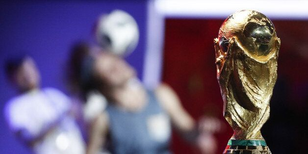 Participants perform near the World Cup trophy during