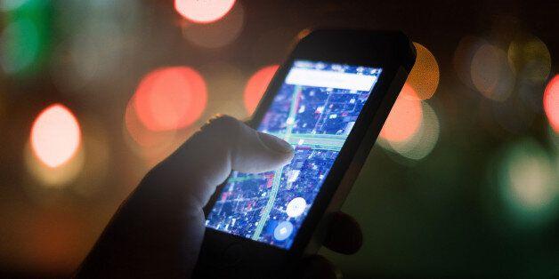 female hand holding smart-phone for order something from web market with bokeh lighting