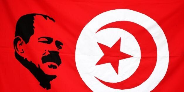An image of prominent opposition figure Chokri Belaid is seen printed on a Tunisian flag as mourners...