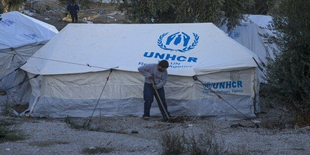LESBOS, GREECE - NOVEMBER 21: A refugee digs with a shover in front of a United Nations High Commissioner...