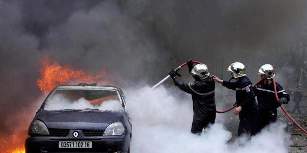 Algiers, ALGERIA: Algerian firemen try to extinguish a burning vehicle after a huge blast in the Government...