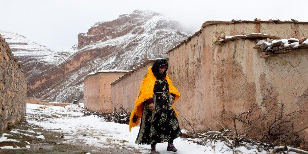 A woman walks through the snow covered village of Tilmi in the High Atlas region of Morocco February...