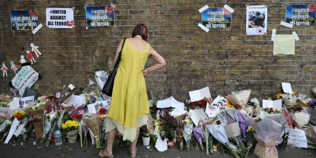 A woman looks at messages at the base of a wall near the scene of an attack next to Finsbury Park Mosque,...