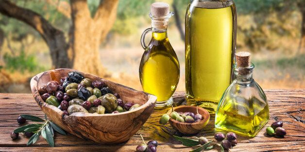 Olives and olive oil in a bottle on the background of the evening olive