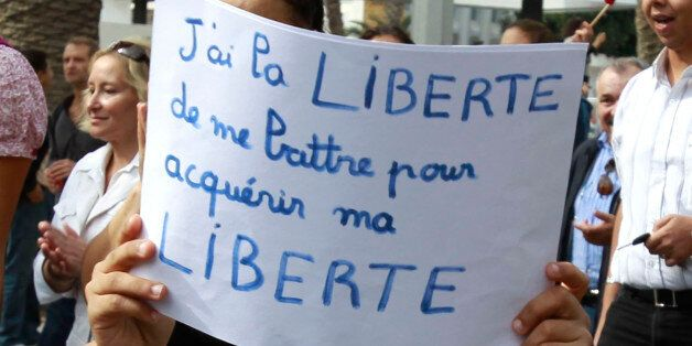 A boy holds a sign during a demonstration against hardline Salafists in Tunis, October 16, 2011. They...