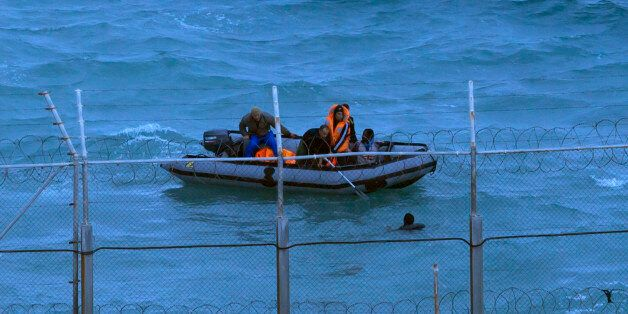 Moroccan soldiers on a boat attempt to board a would-be migrant on Moroccan waters near the border fence...