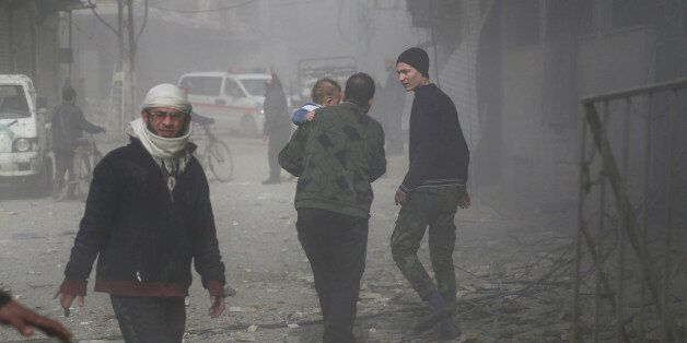An elderly Syrian man carries a child as he walks through the dust following a reported regime air strike...