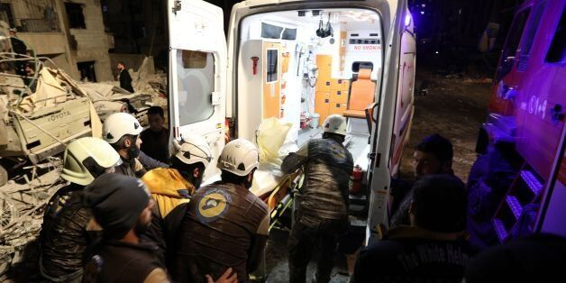 Syrian emergency personnel carry a victim into an ambulance following an explosion at a base for Asian...