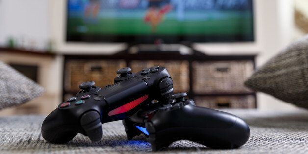 Playing video game. Console controllers or joysticks. Football or soccer game on the television. Widescreen...