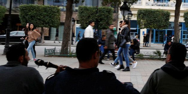 People pass by members of a musical group performing on Habib Bourguiba Avenue in Tunis, Tunisia January...