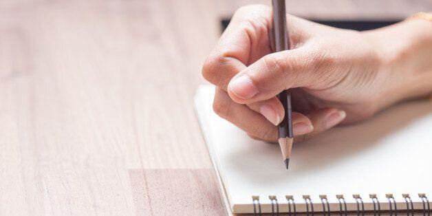 Business women hands working writing on notebook on wooden desk, lighting