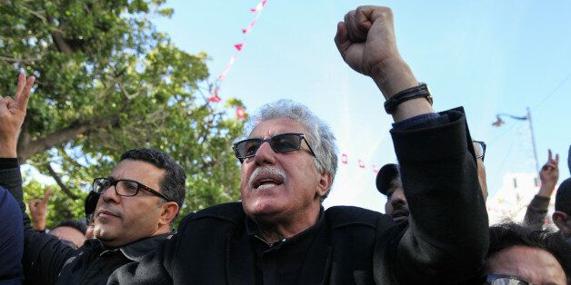 Hamma Hammami (C), leader of the Popular Front, gestures and chant slogans, as he attends the celebration...