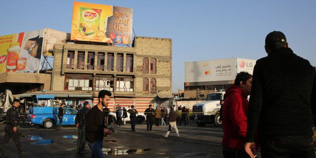 Iraqis walk past the area where a double suicide bombing killed more than 20 people in central Baghdad...
