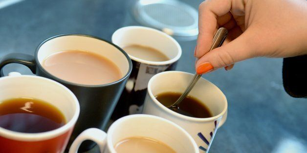 A woman stirs cups of tea and coffee,