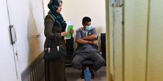 Algerian Abderahman, 47, who had a kidney transplant, stands next to his sister while waiting at Batna's...