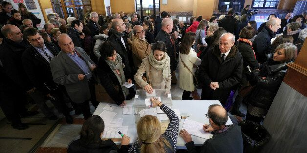 A woman casts her ballot as others wait to vote in Catalonia's regional elections at a polling station...