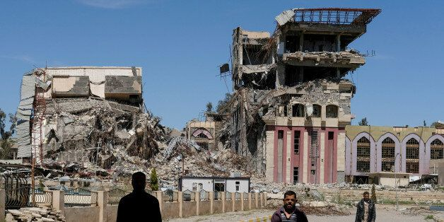 People walk in front of the remains of the University of Mosul, which was burned and destroyed during...