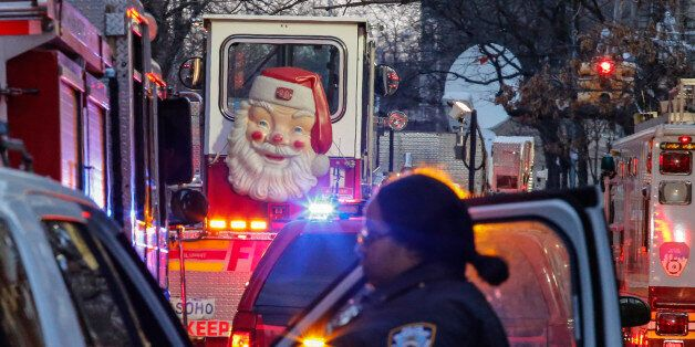 A Santa Claus figure is seen on the door of a fire truck as a New York Police Department (NYPD) officer...