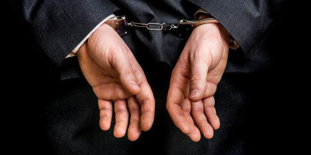 Arrested businessman in handcuffs with hands behind back - isolated on black