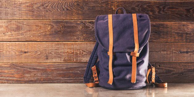 Canvas and leather backpack on wooden