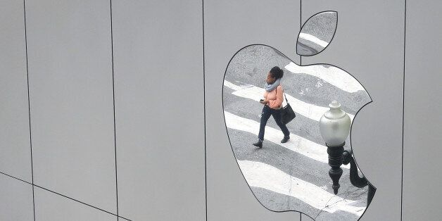 A woman is reflected in a Apple store logo in San Francisco, California, U.S., August 21, 2017. REUTERS/Kevin