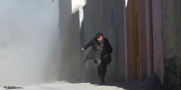 An Afghan man runs away as dust blows in the aftermath of the third blast at a Shiite cultural centre...