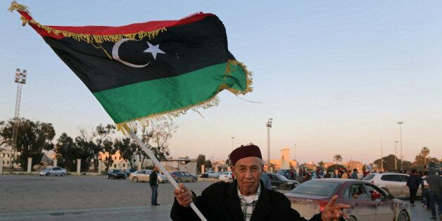 A man holds a Libyan flag as he celebrates the sixth anniversary of the Libyan revolution, in Benghazi,...
