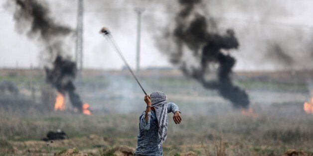GAZA CITY, GAZA - DECEMBER 22 : A Palestinian protester uses slingshot to throw at Israeli security forces...