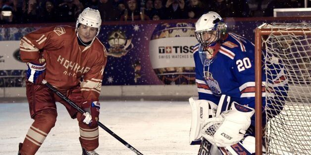 Russian President Vladimir Putin (L) takes part in the Night Hockey League match on the GUM department...