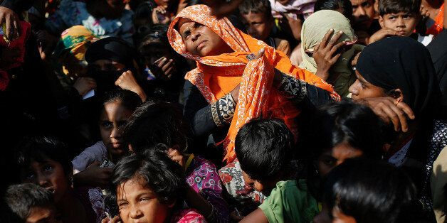 Rohingya refugees wait for a food distribution at the Balukhali refugee camp near Cox's Bazar, Bangladesh...